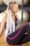 Donna sorridente di forma fisica che si siede in attrezzatura di allenamento alla palestra Fotografie Stock