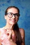 Donna sorridente di pensiero che cerca in vetri Fotografie Stock