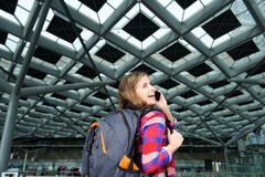 Donna sorridente di viaggio dei giovani con lo zaino ed il telefono cellulare Fotografie Stock