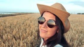 Donna sorridente di viaggio di modo del fronte che corre sul giacimento di grano e sulla testa di giro al tramonto che godono del archivi video