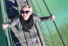 Donna sorridente e di rilassamento felice su una condizione di escursione di un giorno su un vecchio ponte di attaccatura di legn fotografia stock libera da diritti