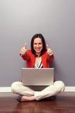 Donna con il computer portatile che dà i pollici su Fotografia Stock