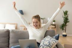 Donna sorridente eccitata che celebra vittoria online, facendo uso del computer portatile a casa fotografie stock libere da diritti
