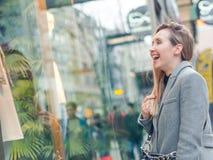Donna sorridente emozionante che esamina una finestra del negozio immagine stock libera da diritti