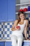 Donna sorridente felice che cucina sulla cucina Immagine Stock Libera da Diritti
