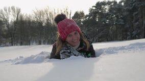 Donna sorridente felice che esamina macchina fotografica lei che si trova sulla neve nell'inverno archivi video