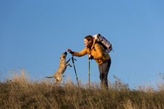 Donna sorridente felice che fa un'escursione in montagne con il cane Fotografia Stock