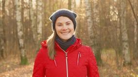 Donna sorridente felice che gode della natura Stando nel parco di autunno Sorridere abbastanza femminile dei giovani alla macchin video d archivio