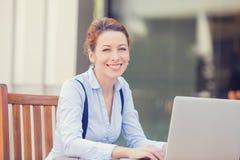 Donna sorridente felice che lavora al computer portatile del computer fuori Fotografia Stock