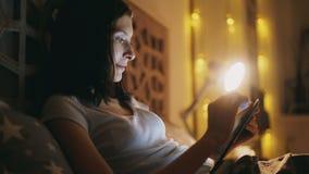 Donna sorridente felice che per mezzo del computer della compressa per la divisione dei media sociali che si trovano a letto a ca fotografie stock libere da diritti