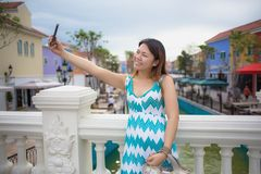 Donna sorridente felice che usando la macchina fotografica del telefono Immagini Stock