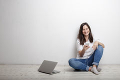 Donna sorridente felice con il cellulare e le cuffie che si siedono vicino alla a Fotografia Stock