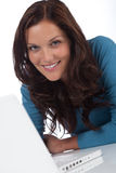 Donna sorridente felice con il computer portatile che esamina macchina fotografica Immagine Stock Libera da Diritti