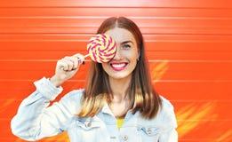 donna sorridente felice con la lecca-lecca dolce del caramello sopra fondo arancio variopinto Fotografia Stock