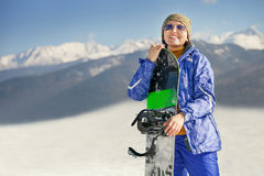Donna sorridente felice con lo snowboard sulla collina della montagna fotografia stock libera da diritti