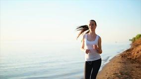 Donna sorridente felice di sport che pareggia sulla spiaggia di sabbia vicino al mare video d archivio