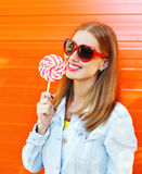 Donna sorridente felice in occhiali da sole con la lecca-lecca dolce sopra fondo arancio variopinto Fotografia Stock Libera da Diritti
