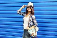 Donna sorridente graziosa che indossa un cappello di paglia, gli occhiali da sole e zaino Fotografie Stock