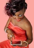 Donna sorridente graziosa che per mezzo di una compressa digitale Fotografie Stock