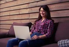 Donna sorridente graziosa che si siede sul sofà con il computer portatile sul suo ginocchio Immagini Stock Libere da Diritti