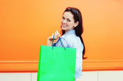Donna sorridente graziosa con il sacchetto della spesa sopra variopinto Fotografie Stock