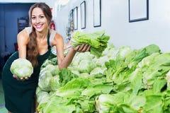 Donna sorridente in grembiule che vende lattuga fresca fotografia stock