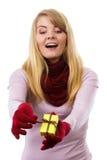 Donna sorridente in guanti di lana che aprono regalo per il Natale o l'altra celebrazione Fotografia Stock Libera da Diritti