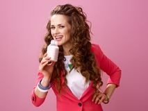 Donna sorridente isolata sul yogurt organico bevente rosa dell'azienda agricola Fotografie Stock Libere da Diritti