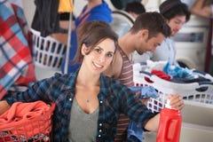 Donna sorridente in lavanderia automatica fotografie stock libere da diritti