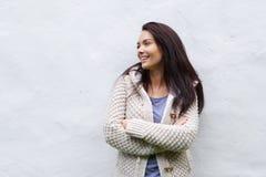 Donna sorridente in maglione della lana che sta contro la parete bianca Immagine Stock
