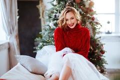 Donna sorridente in maglione rosso sopra il fondo dell'albero di Natale fotografia stock