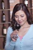Donna sorridente matura con gli occhi chiusi odorando un vetro di vino rosso Fotografie Stock