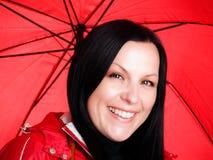 Donna sorridente nella caduta, vestiti rainproof del brunette Fotografia Stock