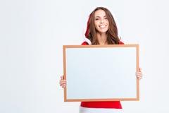 Donna sorridente in panno del Babbo Natale che tiene bordo in bianco Immagine Stock Libera da Diritti