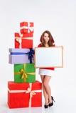 Donna sorridente in panno del Babbo Natale che tiene bordo in bianco Fotografia Stock Libera da Diritti