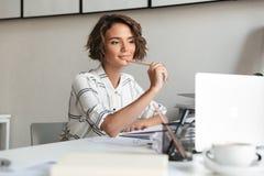 Donna sorridente premurosa che lavora dalla tavola Immagini Stock