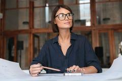 Donna sorridente premurosa di affari in occhiali che si siedono dalla tavola Fotografia Stock