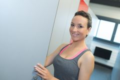 Donna sorridente pronta per l'allenamento nello spogliatoio della palestra Immagine Stock