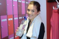 Donna sorridente pronta per l'allenamento nello spogliatoio della palestra Immagini Stock