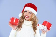 Donna sorridente in regali di natale della holding del cappello della Santa Fotografie Stock