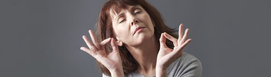 Donna sorridente 50s che medita e che si rilassa con l'yoga, insegna grigia Fotografia Stock Libera da Diritti