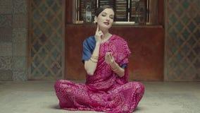 Donna sorridente in sari che applicano profumo asciutto sul collo stock footage