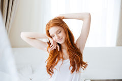 Donna sorridente sensuale che si siede e che allunga a letto Fotografia Stock Libera da Diritti