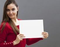 Donna sorridente sexy 20s che fa una pubblicità nella visualizzazione dell'inserzione in bianco accanto lei Immagine Stock Libera da Diritti