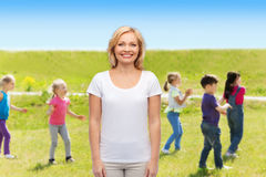 Donna sorridente sopra il gruppo di bambini all'aperto Fotografia Stock Libera da Diritti