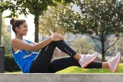 Donna sorridente sportiva che fa gli allungamenti prima dell'esercitazione nel parco Fotografie Stock Libere da Diritti