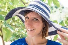 Donna sorridente in un cappellino da sole elegante Fotografia Stock Libera da Diritti