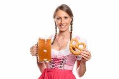 Donna sorridente in un dirndl con una birra e una ciambellina salata Fotografie Stock
