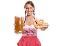 Donna sorridente in un dirndl con una birra e una ciambellina salata Immagine Stock