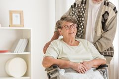 Donna sorridente in un distogliere lo sguardo della sedia a rotelle Di sostegno dal suo marito fotografia stock